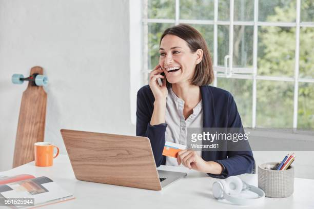 laughing businesswoman on cell phone at desk holding card - charging sports stock pictures, royalty-free photos & images