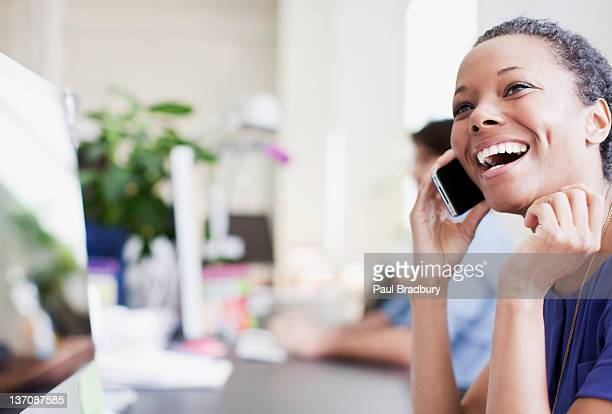 Laughing businesswoman talking on cell phone in office