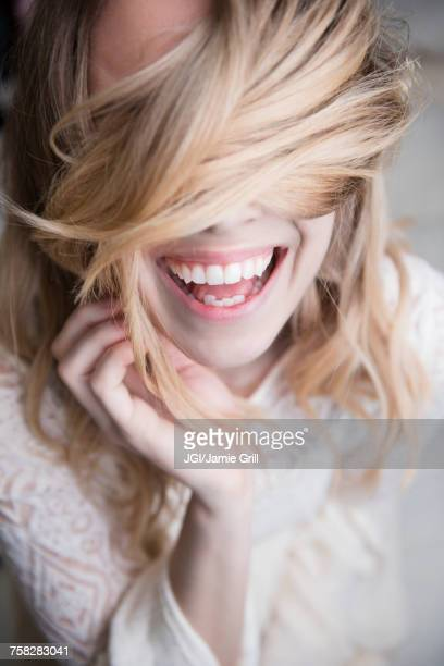 Laughing Caucasian woman covering eyes with hair