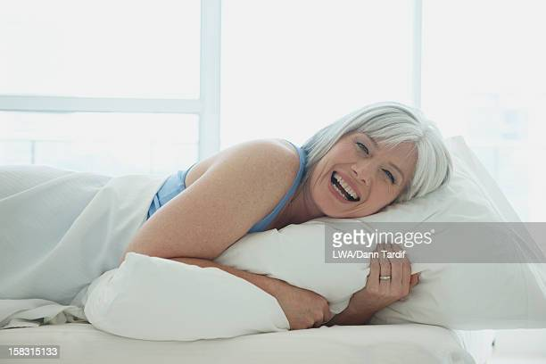 Laughing Caucasian woman laying in bed