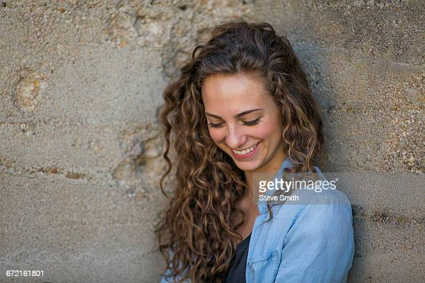 Laughing Caucasian woman leaning on concrete wall