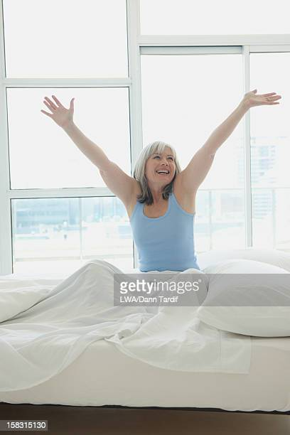 Laughing Caucasian woman sitting in bed
