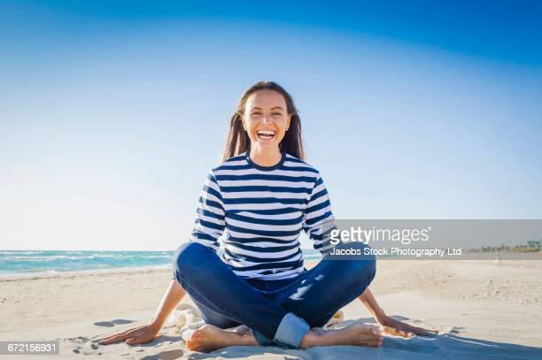 Laughing Caucasian woman sitting on sand at beach