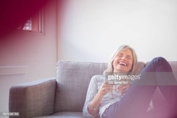 Laughing Caucasian woman sitting on sofa drinking coffee