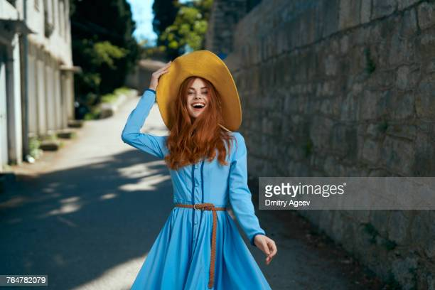 laughing caucasian woman wearing hat near stone wall - strohoed stockfoto's en -beelden