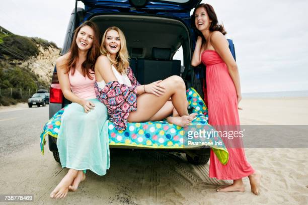 Laughing Caucasian women at hatch of car on beach