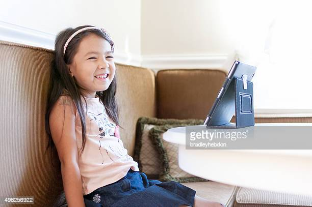Laughing cheerful little girl sitting at kitchen table with iPad