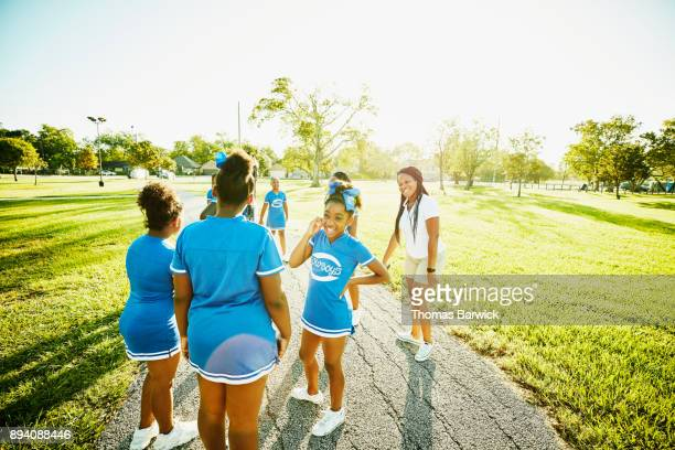 laughing cheerleaders listening to coach during early morning practice in park - black cheerleaders stock photos and pictures