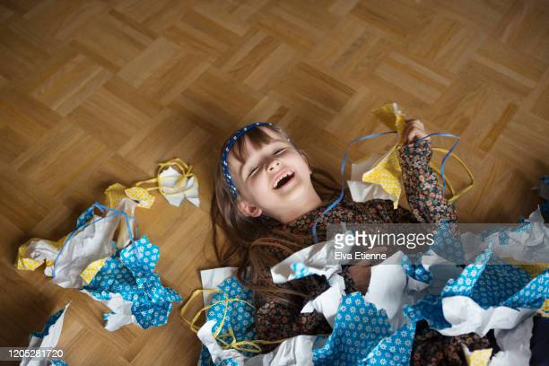 laughing child (6-7) lying on the floor surrounded by discarded wrapping paper after a birthday celebration - after party stockfoto's en -beelden