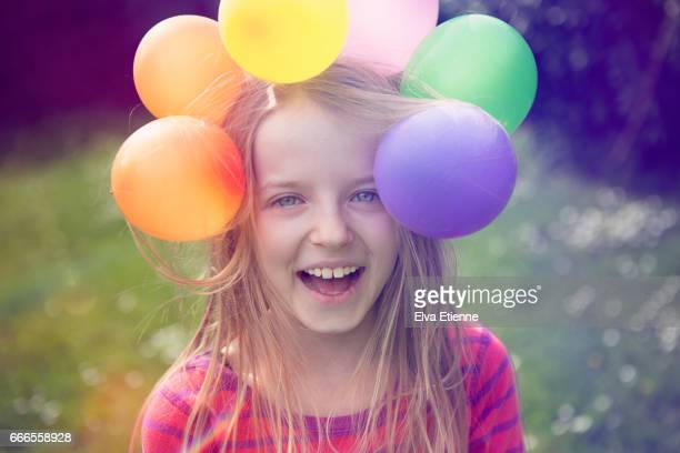 Laughing child with balloons stuck on her head