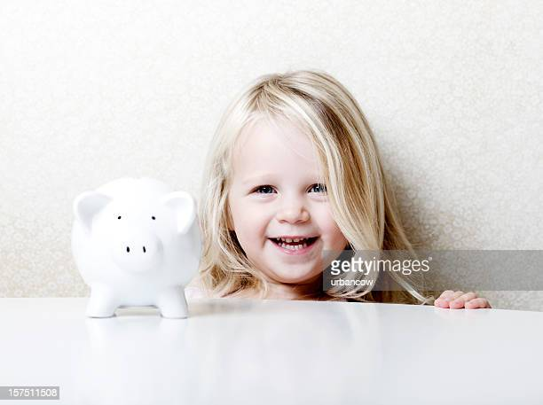 Laughing child with piggy bank