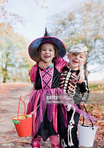 laughing children in halloween costumes - halloween kids stock photos and pictures