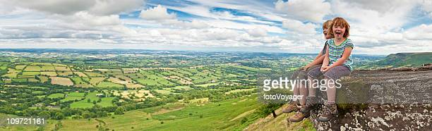 Laughing children on mountain top overlooking green summer landscape panorama