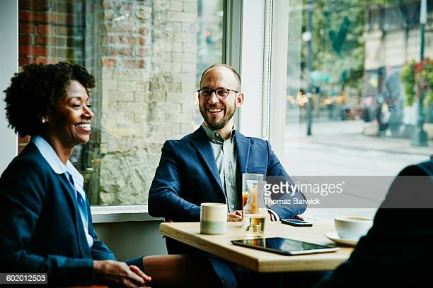 Laughing colleagues in discussion in cafe