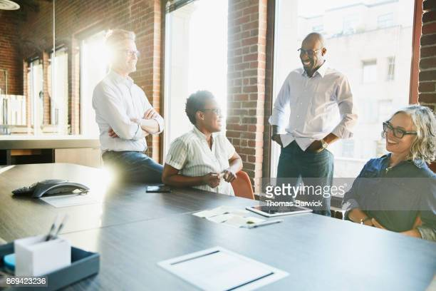 laughing colleagues in project planning meeting in office conference room - businesswear stock pictures, royalty-free photos & images