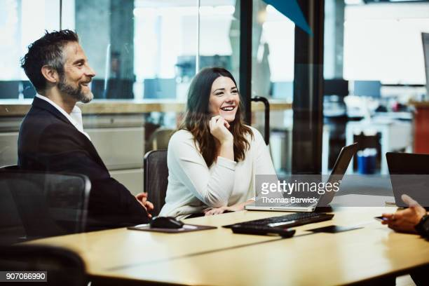 Laughing colleagues meeting with clients in office conference room