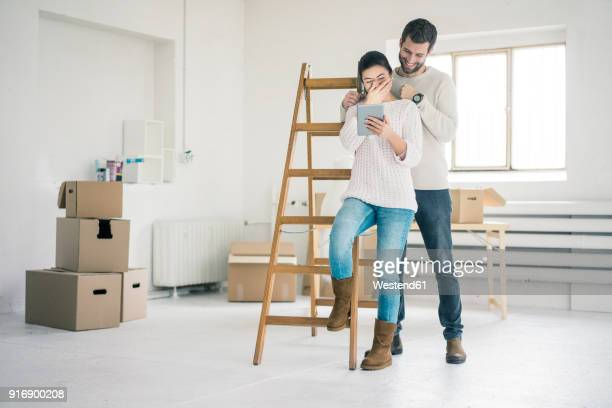 Laughing couple at ladder in new home looking at tablet