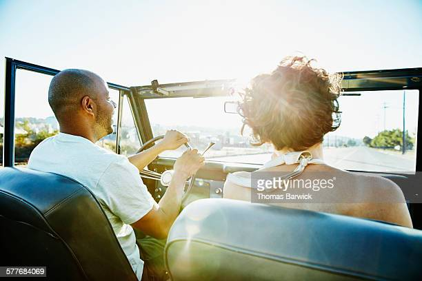 Laughing couple driving convertible