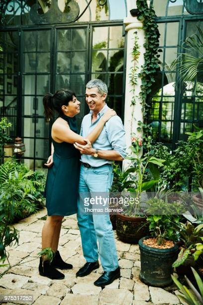 Laughing couple embracing in garden courtyard of home on summer evening