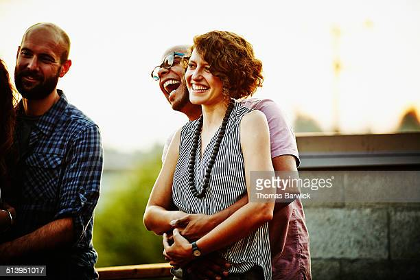 Laughing couple embracing on rooftop deck