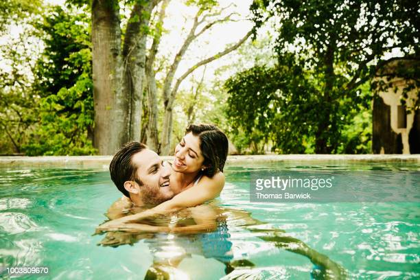 Laughing couple embracing while relaxing in plunge pool at luxury resort