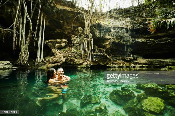Laughing couple embracing while swimming in cenote