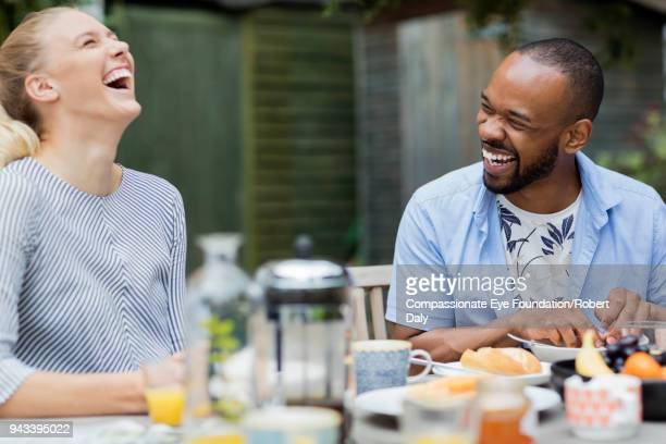 laughing couple having breakfast on patio - head back stock pictures, royalty-free photos & images