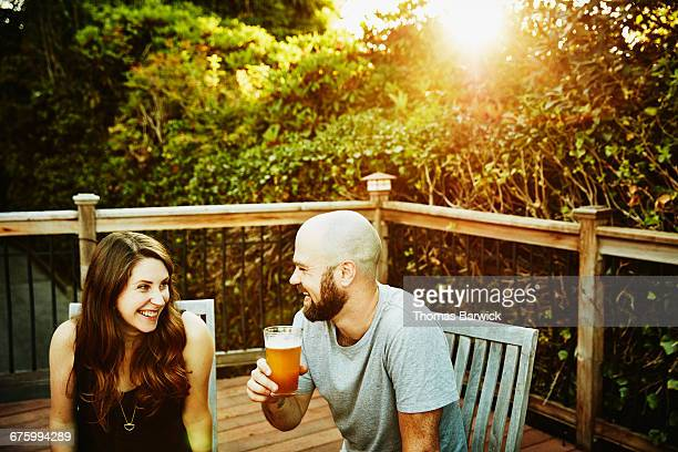 Laughing couple having drinks on backyard deck