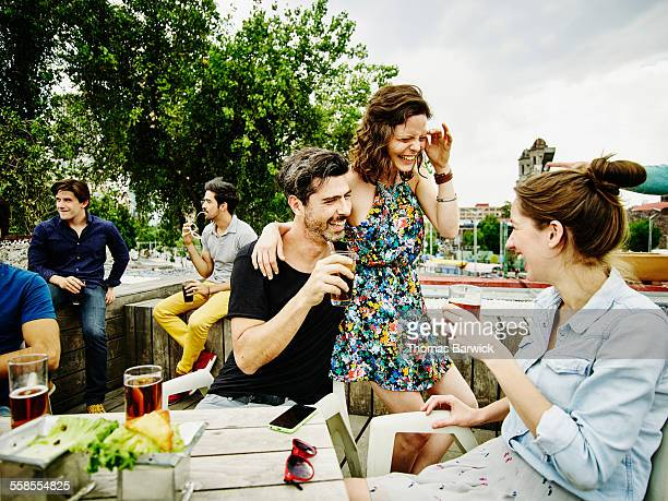 Laughing couple having drinks with friends
