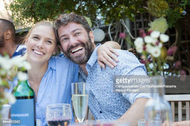 laughing couple having lunch with friends on garden patio - garden party stock pictures, royalty-free photos & images