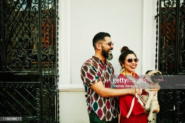 laughing couple holding dog while walking through town - nosotroscollection stock pictures, royalty-free photos & images
