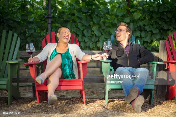 laughing couple holding hands and drinking wine on a sunny afternoon - sonoma county stock pictures, royalty-free photos & images