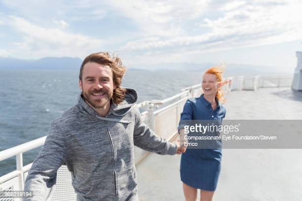 Laughing couple holding hands on boat deck