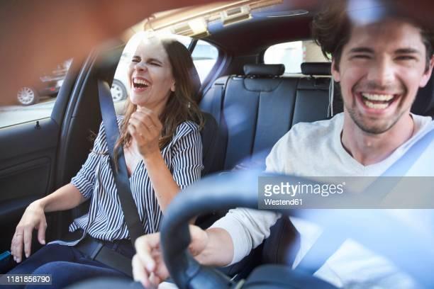 laughing couple in a car with man driving - landvoertuig stockfoto's en -beelden