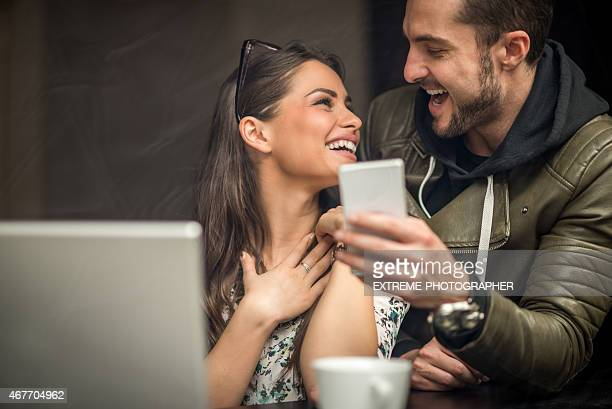 Laughing couple in coffee shop looking at mobile device