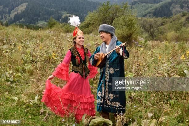 Laughing couple in traditional Kazakh clothing in a field at Huns village Kazakhstan