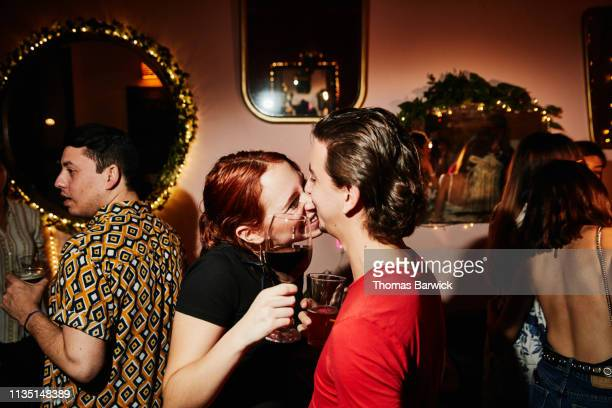 Laughing couple kissing while on date in night club