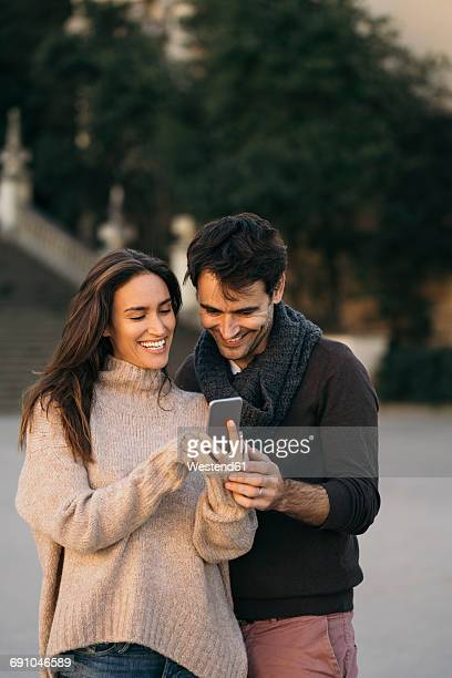 laughing couple looking at cell phone - zuid europese etniciteit stockfoto's en -beelden