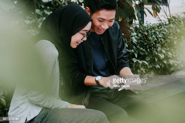 laughing couple looking at phone - rifka hayati stock pictures, royalty-free photos & images