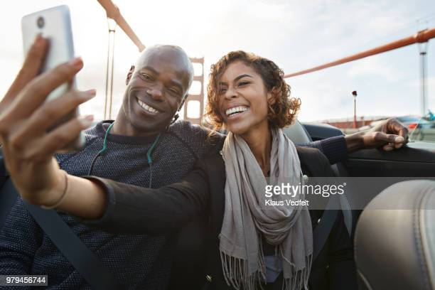 laughing couple making selfie on the back seat of convertible car - interracial wife stock pictures, royalty-free photos & images