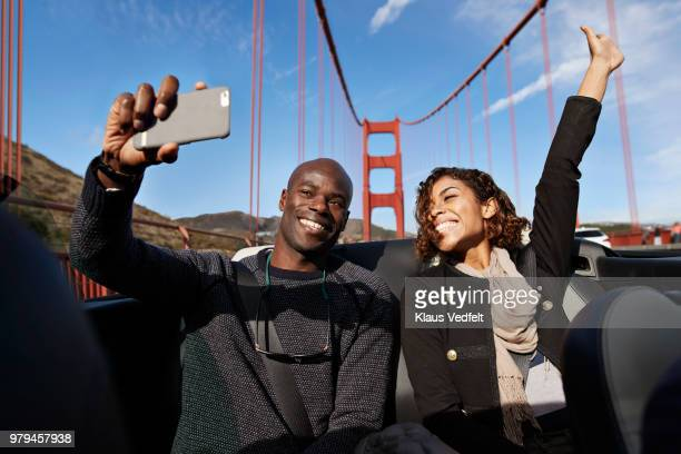 Laughing couple making selfie on the back seat of convertible car
