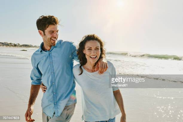laughing couple on the beach - ehefrau stock-fotos und bilder