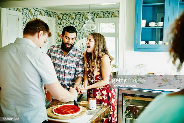 laughing couple preparing pizza with friends - ディナーパーティー ストックフォトと画像
