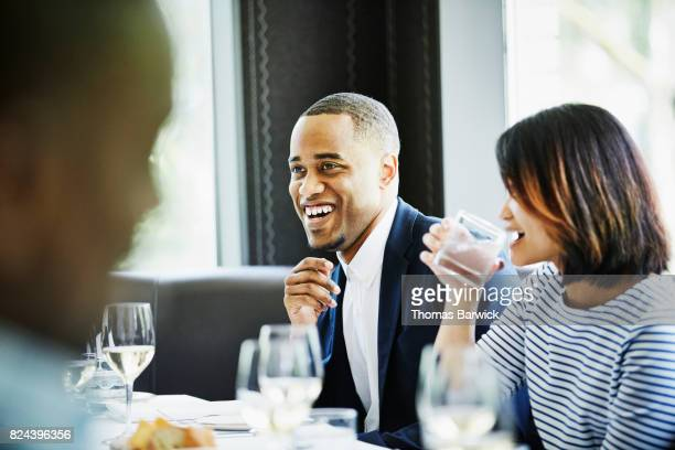 Laughing couple sharing a meal with family and friends in restaurant