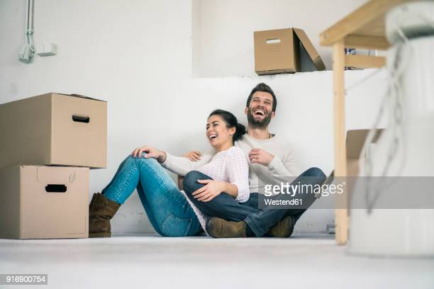 laughing couple sitting in new home surrounded by cardboard boxes - demenagement humour photos et images de collection