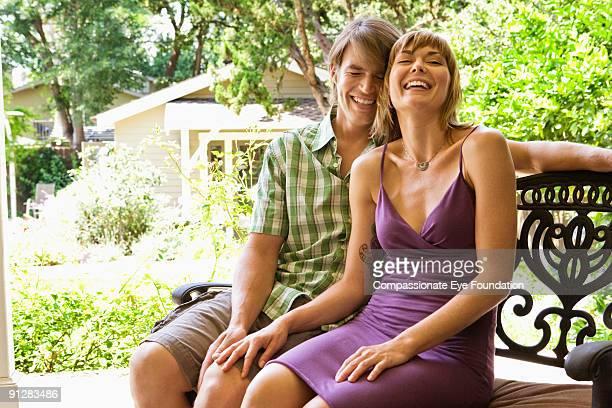 "laughing couple sitting on bench - ""compassionate eye"" imagens e fotografias de stock"