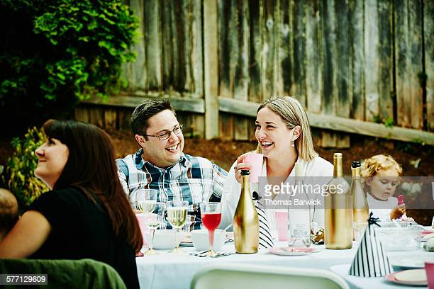 Laughing couple sitting with friends and family