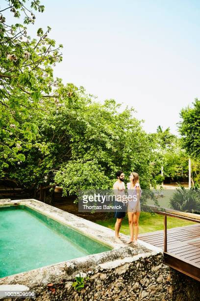 Laughing couple standing on edge of plunge pool at luxury tropical resort