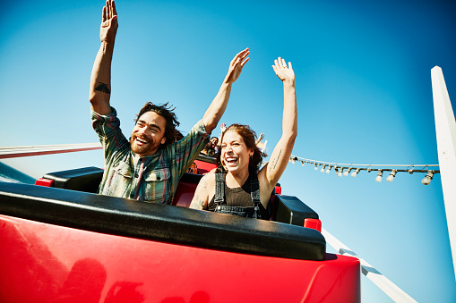 Laughing couple with arms raised riding roller coaster - gettyimageskorea