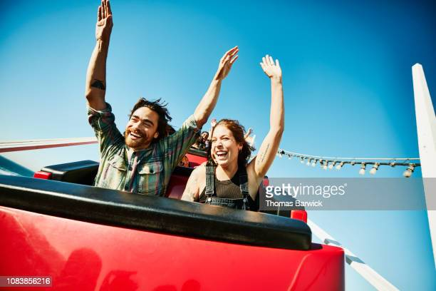 laughing couple with arms raised riding roller coaster - lol stock photos and pictures